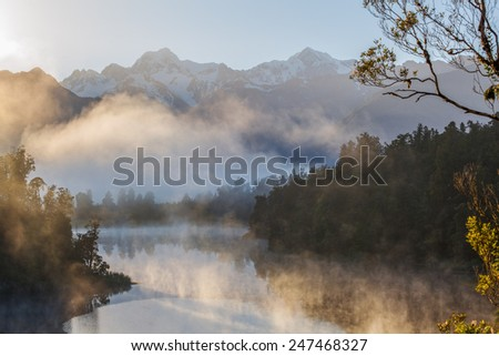 View of Southern Alps from lake Matheson in the early morning mist. South Island, New Zealand. - stock photo