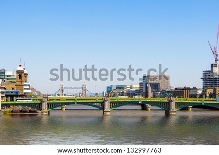 View of Southwark Bridge against the backdrop of Tower Bridge and a beautiful sky. - stock photo