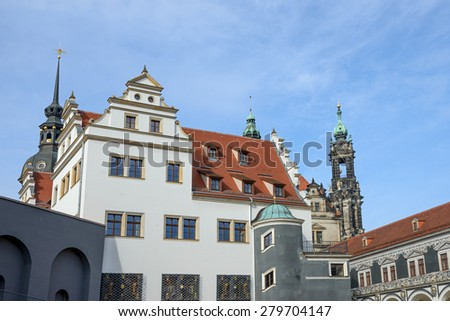 View of Stables Courtyard (Stallhof) with Chancellery Building on foreground and George Gate, tops of bell tower of Dresden Cathedral and Hausmannsturm tower on background in Dresden, Saxony, Germany. - stock photo