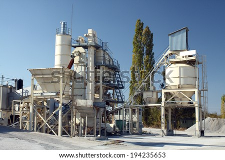 View of stone quarry with silos - stock photo