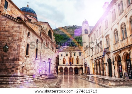 View of streets of old fortress in Dubrovnik, Croatia. Lens flare, sunlight, cloudy weather, after rain - stock photo