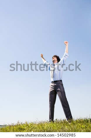 View of successful manager lifting up arms and standing on the grass - stock photo