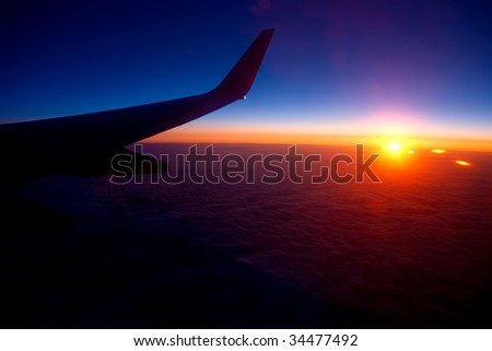 View of sunrise above cloudy horizon from airplane - stock photo