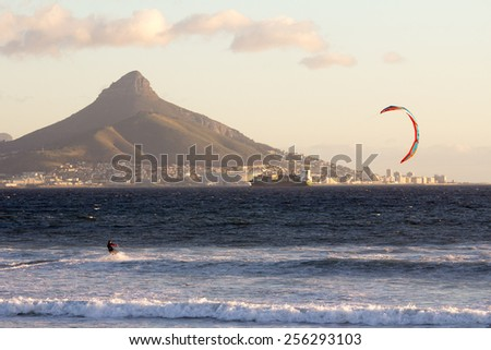 View of table mountain from Dolphin Beach with windsurfer having fun - stock photo