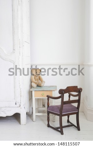 View of teddy bear on child's study table by wardrobe - stock photo