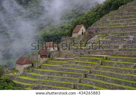 View of terraces of Lost Inca City of Machu Picchu. Low clouds. Cusco Region,Sacred Valley, Peru - stock photo