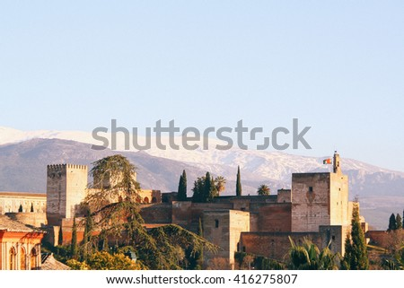View of the Alhambra (Granada, Spain) on top of a hill, with the Sierra Nevada mountain range in the background. - stock photo
