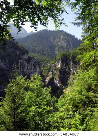 View of the Alps and the suspension bridge in the gorge from the world-famous Bavarian castle Hohenschwangau - stock photo