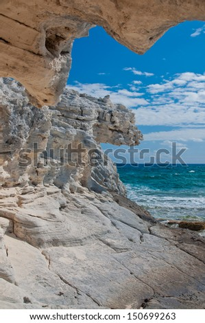 view of the atlantic ocean from inside a rock formation that is shaped like a heart.  Islands of the bahamas - stock photo