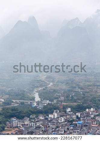 View of the beautiful mountains from the hill in the town of Hingping in the mist - China - stock photo