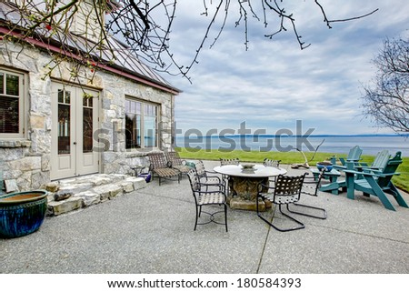 VIew of the big stone house with concrete floor patio area. Patio table set and deck chairs. - stock photo