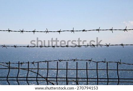 View of the blue sea through the barbed wire - stock photo
