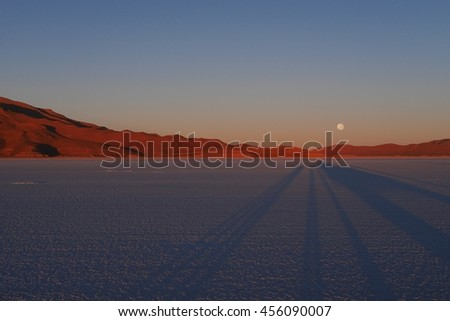 View of the Bolivian Salt Flats with the Moon Setting. Salar de Uyuni, Bolivia, South America - stock photo