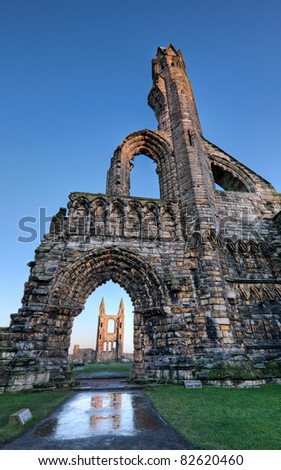 View of the cathedral in St Andrews, Fife, looking towards the east gable, framed by the arch in the west gate. - stock photo