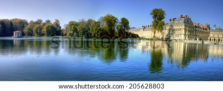 View of the Chateau de Fontainbleu and its reflection across a tranquil lake, situated close to Paris it introduced the Mannerist style of architecture to France and is the largest royal chateau - stock photo