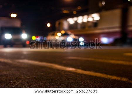 View of the city at night, the cars driving on the road. View from the curb at the asphalt level - stock photo