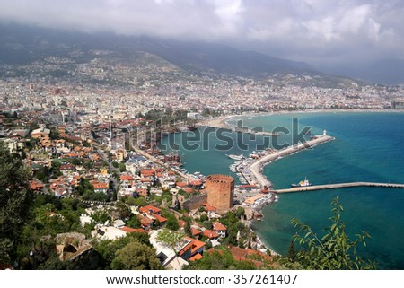View of the city of Alanya, castle, red tower, dock, ships - stock photo