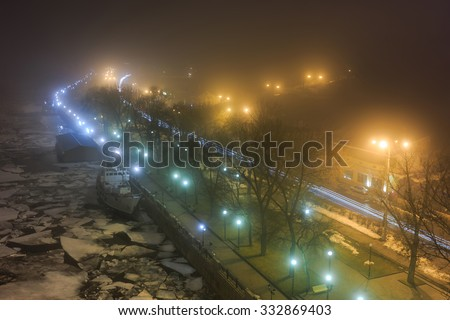 View of the city waterfront winter night. Lantern light, seen on the river ice, fog. Taken from above. Urban background. An empty street, night lights lanterns. - stock photo