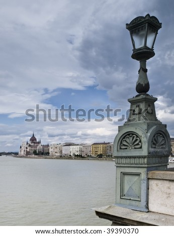 View of the Danube River from the famous Chain Bridge in Budapest, with a lamppost included in the foreground of the composition and the Parliament Building in the background - stock photo