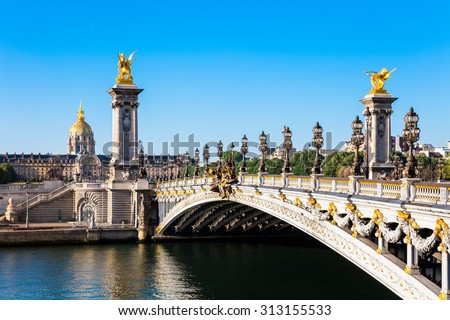 View of the Dome des Invalides from the Pont Alexandre III bridge in the summer morning. Pont Alexandre III bridge decorated with ornate Art Nouveau lamps and sculptures. - stock photo