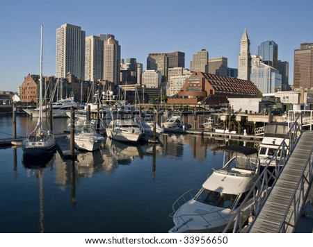 View of the downtown of Boston (USA) from a pier of the maritime district, with some boats on the foreground and the skyline of the city on the background - stock photo