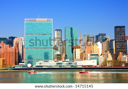View of the east river and Manhattan skyline featuring the United Nations building. - stock photo