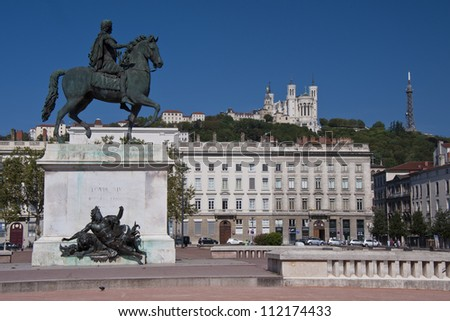 view of the equestrian statue of louis xiv and the basilica of notre dame de fourviere from place bellecour, in the center of lyon - stock photo