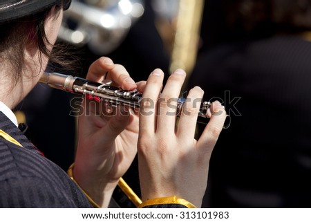 View of the fingers of a young woman playing a flute on a dark background. Girl playing a flute.  - stock photo