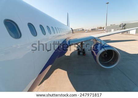 View of the fuselage, porthole and aircrafts wing - stock photo