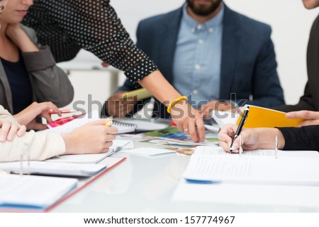 View of the hands of a group of young people in a business meeting analyzing paperwork and planning a new business strategy - stock photo