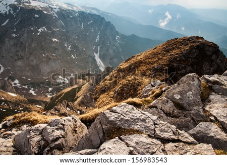 View of the high mountains with rocks on the foreground. Last rays of the sun in tatras - stock photo