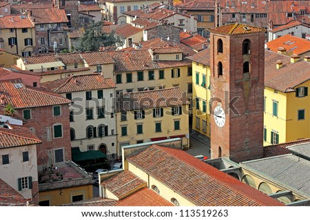 View of the historic part of Lucca in Italy, with an old clock tower and the narrow streets. - stock photo