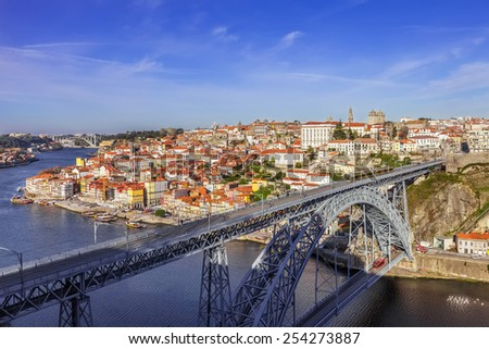 View of the iconic Dom Luis I bridge crossing the Douro River, and the historical Ribeira and Se District in the city of Porto, Portugal. Unesco World Heritage Site. - stock photo