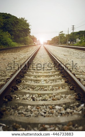 "view of the length of railway with green tree at left and right side of railway,filtered image, light effect and flare added,selective focus,mean ""There light at the end of the tunnel"", success way - stock photo"