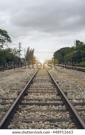 "view of the length of railway with green tree at left and right side of railway,filtered image, light effect and flare added,selective focus,mean ""Theres light at the end of the tunnel"", success way - stock photo"