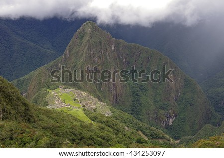 View of the Lost Incan City of Machu Picchu and Huayna Picchu mountain .Low clouds .Cusco Region,Sacred Valley, Peru - stock photo