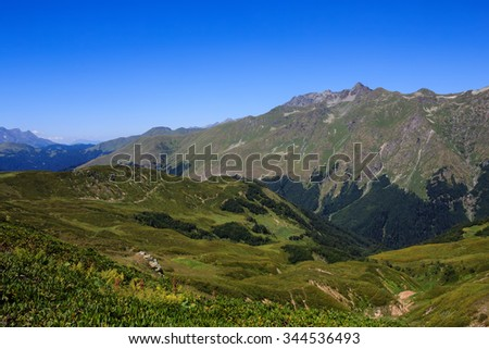 view of The Main Caucasian Ridge with rocky mountains and alpine meadows with rhododendron flowers and evergreen forest - stock photo
