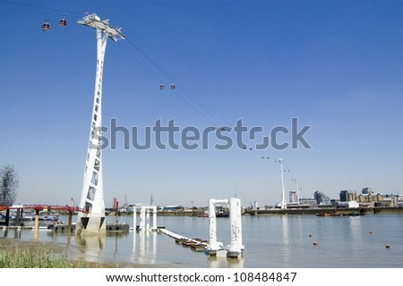 View of the new cable car public transport link between Greenwich and Docklands in the East of London.   View from public footpath. - stock photo