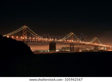 View of the Oakland-San Francisco Bay bridge at night from Treasure island - stock photo