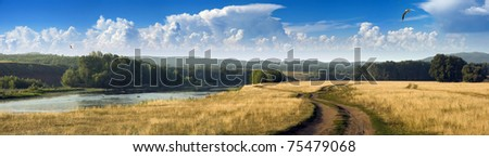 View of the plain of river and dirt road during a hot summer day. - stock photo