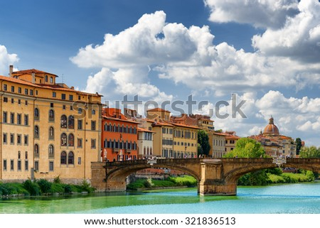 View of the Ponte Santa Trinita (Holy Trinity Bridge) over the Arno River in Florence, Tuscany, Italy. Dome of the Church of Saint Fridianus (San Frediano in Cestello) is visible in background. - stock photo