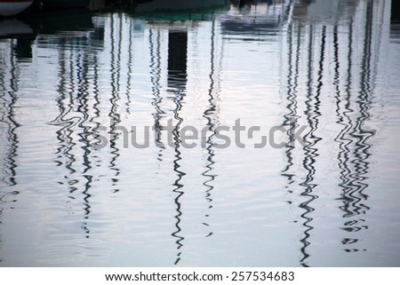 View of the reflection on the water of the boats docked. - stock photo
