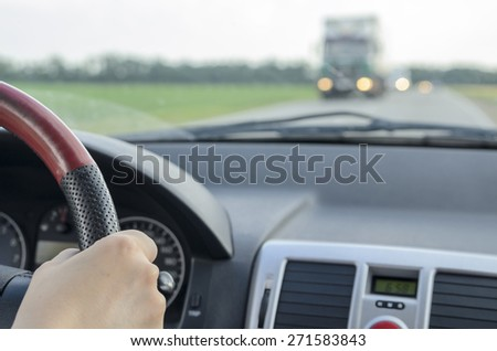 view of the road and oncoming traffic from a moving car - stock photo