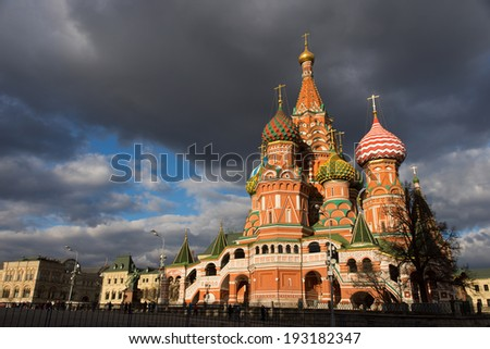 View of the Saint Basil's Cathedral, blue sky and dark clouds background. Moscow, Russia. - stock photo