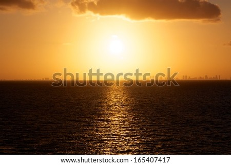 View of the setting sun over the ocean with the skyline of Miami, FL, USA in the distance. - stock photo