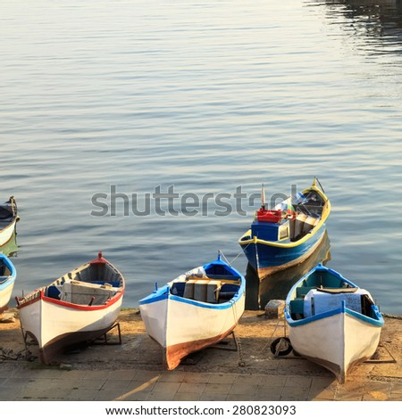 View of the southern harbor of the old town of Nessebar at sunset, with fishing boats in the foreground,  Black sea coast, Bulgaria. - stock photo