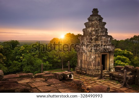 View of the sun setting over the Cambodian countryside from the summit of Phnom Bakheng. - stock photo