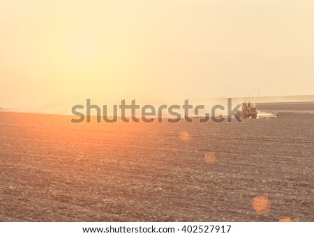 View of the tractor working in the agricultural field. Toned - stock photo