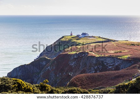 View of the trails on Howth Cliffs and Howth Head with the Baily Lighthouse and the Irish sea in the background in Ireland - stock photo