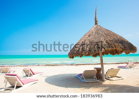 view of the tropical beach with umbrella and multiple beds - stock photo